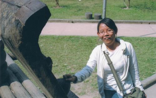 Trang de l'ethnie édé pose sa main sur un sein en bois. Oh la la !