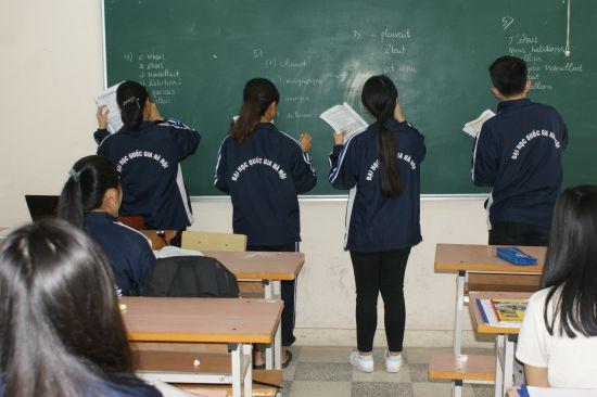 Trois étudiantes et un étudiant au tableau