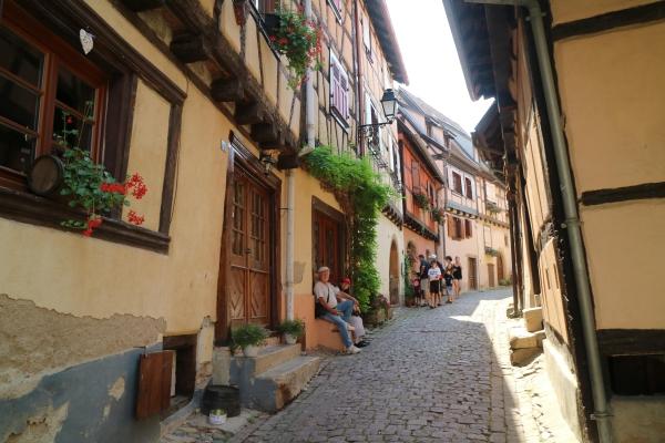 « Au village d'Eguisheim. Quel plaisir de retrouver l'Alsace et les maisons à colombages en été ! Jean et Marie-Ange - assis à gauche -m'attendaient un peu plus loin. Ils étaient un peu fatigués à cause de la chaleur. »