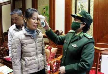 Vérification de la température corporelle d'une passagère à la porte frontière de Mong Cai, province de Quang Ninh